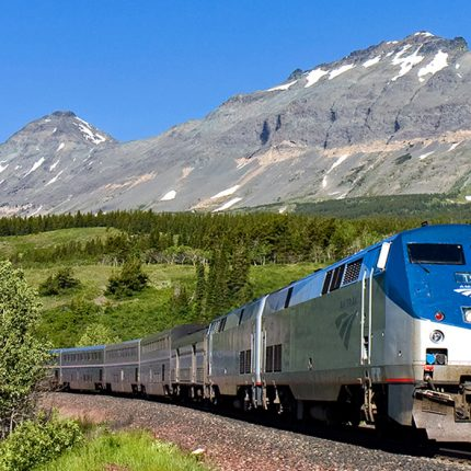 Amtrak train with snow capped mountains in the background
